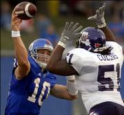 Kansas quarterback Kerry Meier attempts to pass around the oncoming rush of Northwestern State defensive tackle Tory Collins during the first half of Saturday night's game at Memorial Stadium.