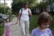 From left, Olive Olson, 5, walks with her mother, Stefanie, and sister, Annie, 7, to New York School, 936 N.Y. Parents and students are barred from using the newly renovated front entrance of the school, frustrating parents and students alike. The Olson family walked to the East Lawrence school on Friday morning.