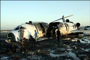 Iranian officials examine the site of a plane crash at the airport in the city of Mashhad, 620 miles northeast of Tehran. A jetliner blew a tire, skidded off a runway and caught fire while landing Friday, killing 29 people.