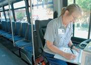 Lawrence Transit System driver Debra Rodman, Perry, logs mileage into her notebook. City officials are beginning to research energy-efficient buses now in development.