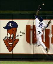 Kansas City left fielder Emil Brown climbs the wall but comes up short as he attempts to catch a home-run ball hit by New York's Jorge Posada in the eighth inning. The Yankees scored 10 runs that inning to rally past the Royals, 12-5, on Monday in Kansas City, Mo.