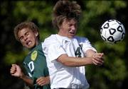 Free State defender Travis Everett, right, and Shawnee Mission South midfielder Christian Duke go up for a header. The Raiders beat the Firebirds, 4-1, Tuesday at FSHS.