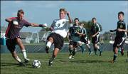 Free State High midfielder Andrew Heck (9) chases a loose ball with Shawnee Mission South goalkeeper Chris Marx, left. The Firebirds lost, 4-1, Tuesday at Free State.