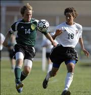 Free State High forward Erik Slan, right, and Shawnee Mission South defender Shane Shulze fight for a loose ball. The Raiders defeated the Firebirds, 4-1, Tuesday at Free State.