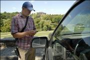 Alan Bloomquist, Kansas University senior, tickets a vehicle without a parking pass on Memorial Drive on the KU campus. Bloomquist works part-time for KU's parking and transit department and was patrolling for parking violators Tuesday.