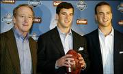 Father Archie Manning, left, and sons Eli, center, and Peyton pose for a picture in this file photo from 2004. The Manning siblings will meet in the Brothers Bowl on Sunday in New York, when Eli's Giants play host to Peyton's Indianapolis Colts.