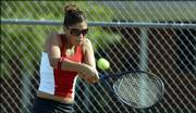 Lawrence High senior Lauren Kelly returns a serve during her first match of the season. Kelly lost twice at Wednesday's tennis triangular at the Lawrence Tennis Center.