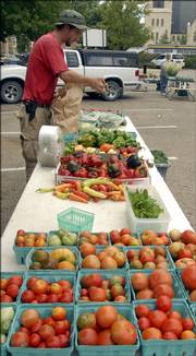 Avery Lominska sets out produce for customers at the Lawrence Farmers Market, 1020 Vt. He is the son of Bob Lominska, who continues gardening throughout fall.