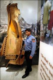 Ron Parker, a first responder on Sept. 11, 2001, and now a tour guide at ground zero, stands next to a twisted beam from the World Trade Center site in the new Tribute WTC Visitor Center. The center opened to private visits from victims' families, Sept. 11 survivors and recovery workers on Wednesday. It opens to the public on Sept. 18.