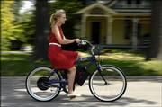 Crystal White, 20, a Kansas University senior from Lubbock, Texas, takes a spin on a Giant bicycle that has been modified into an electric-powered vehicle. Del Christensen, Lawrence, is building and marketing the bicycles, which are powered by four batteries and can reach 35 mph.