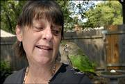 Lawrence resident Val Shelton is thankful for the restorative work she has gotten at the Douglas County Dental Clinic, a United Way agency. At her home in East Lawrence, Shelton enjoys the company of her brown-headed parrot Clover.