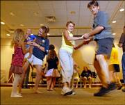 Carla Mumma and Jerry Jost, right, dance down the line of people at the 10th anniversary of the Lawrence Barn Dance Assn. The event was Aug. 26 at the Lawrence Public Library, 707 Vt.