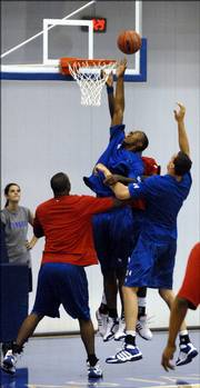 Kansas University freshman Darrell Arthur goes up for a putback attempt over the other Jayhawk big men. The Jayhawks held a blue-and-red scrimmage in mid-June at the Bill Self basketball camp in Horejsi Family Athletics Center.