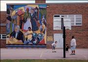 "Children play at Cordley School, 1837 Vt., with Dave Loewenstein&squot;s mural ""A Thousand Miles Away"" towering overhead. The mural is one of several Lawrence artworks highlighted in ""Kansas Murals: A Traveler&squot;s Guide,"" written by Loewenstein and Lora Jost."