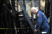An ATF agent examines the Glover home, looking for the cause of the fatal fire in the 1200 block of New Jersey.