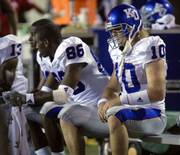 Kansas University quarterback Kerry Meier, right, sits on the Jayhawks' bench during Friday's 37-31 loss to Toledo. Meier was injured during the fourth quarter but re-entered the game.