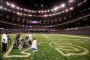 Grounds crews paint the end zones of the Louisiana Superdome on Monday. Next week, the New Orleans Saints will play the first game in their home stadium since it was damaged by Hurricane Katrina.