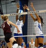 Texas A&M's Christi Hahn (14) spikes through the block attempt of Kansas' Brittany Williams (10) and Jana Correa. Regardless, the Jayhawks beat the Aggies, 3-2, on Wednesday at Horejsi Center.