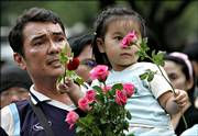 "A Thai man brings his young daughter to hand out roses to soldiers involved in the military coup in Bangkok, Thailand. Army chief Gen. Sondhi Boonyaratkalin, who led the coup ousting Prime Minister Thaksin Shinawatra, told a news conference that he would act as prime minister for two weeks until a new leader ""who is neutral and upholds democracy"" is found. The new government would not hold on to power for more than a year, he said."