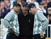 U.S. captain Tom Lehman, center, speaks to Tiger Woods, left, and Jim Furyk on the first tee before the start of play Friday. Woods and Furyk scored a fourball victory against Europe's Colin Montgomerie and Padraig Harrington.