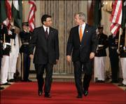 President Bush walks with Pakistan President Gen. Pervez Musharraf to the East Room at the White House on Friday to hold a news conference. Bush met Friday with Musharraf, who has claimed a U.S. official threatened an attack on his Muslim nation if it did not cooperate in the war on terror.