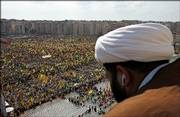 "A Shiite Muslim Sheik watches as Hezbollah supporters wave their group&squot;s flags Friday during a Hezbollah ""victory"" rally, in Beirut&squot;s bombed-out suburbs, Lebanon. Hezbollah&squot;s leader Sheik Hassan Nasrallah made his first public appearance since his group&squot;s war with Israel began July 12, taking the stage Friday before the gigantic rally."