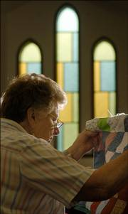 Lorene Davison checks her quilt work during a work session at Central United Methodist Church, 1501 Mass.