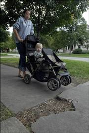 Chrissy Whetter, Lawrence, avoids a piece of broken sidewalk near 13th and Massachusetts as she pushes Jacob Goans-Heinz, 1, in his stroller. The city of Lawrence has released a map highlighting the best and worst sidewalks, such as this stretch of sidewalk, in Lawrence.