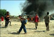 Children throw stones at a burning vehicle after a roadside bomb attack Sunday, in Baqouba, Iraq, 35 miles northeast of Baghdad. Insurgents attacked a convoy of two vehicles allegedly of foreign contractors, seriously damaging one with a roadside bomb and wounding its four occupants.