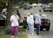 Bystanders pace the scene of a Sunday shooting in the Mobile Village trailer park at 110 N. Mich. The shooting of a 36-year-old woman followed an hourslong standoff with police.