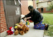 Shawn Crawford places stuffed animals in front of an apartment Sunday in the John DeShields public housing complex in East St. Louis, Ill., near where three children were found slain Saturday. This struggling community turned to prayer Sunday in trying to understand the slaying of a pregnant mother, whose fetus was cut from her womb, and her three children, who were found stuffed in their apartment's washer and dryer.