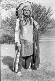 "William ""Lone Star"" Dietz, wearing sioux indian regalia, poses in front of the Haskell Institute on Oct. 24, 1932. Dietz, according to a new biography, was raised by two white parents but believed he had Sioux blood. He is credited for inspiring the name of the Washington Redskins. Below, the cover of the St. Louis Globe-Democrat Sunday supplement on Jan. 26, 1908, portrays Dietz."