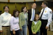 As the Corliss family gathers for a photo, Lawrence-Douglas County Fire & Medical Chief Mark Bradford, right, jumps into the photograph next to David Corliss. Corliss was installed as the new city manager of Lawrence on Friday at City Hall in front of city employees, friends and family. Corliss was most recently interim city manager. The Corliss family is, from left, his wife, Sarah, and daughters Emily, 16, Katherine, 13, and Laura, 10.
