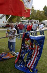 NASCAR fans and friends of Sonny Sales, Crescent, Iowa, left, watch as Sales raises a flag pole with an assortment of racing flags at the Lawrence KOA Campground, 1473 U.S. Highway 40. Racing fans were gathering Friday around Lawrence for a weekend of NASCAR events at the Kansas Speedway.