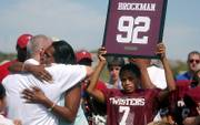 Twisters player Trent Jefferson holds up the jersey number of his teammate and cousin, DaVonte Brockman, as DaVonte's aunt, Diana Glover, hugs Bret Toelkes, president of the Lawrence Youth Football League, at a ceremony Sunday to retire DaVonte's jersey number, 92. DaVonte died in a house fire, along with four other family members, Sept. 17. The ceremony took place during halftime of the Twisters' football game at the Youth Sports Inc. complex.