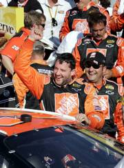 Tony Stewart celebrates with teammates in Victory Lane. Stewart won the Banquet 400 on Sunday at Kansas Speedway.