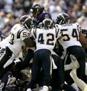 Baltimore ravens running back Jamal Lewis, top, is stopped by San Diego's Randall Godfrey, left, Clinton Hart, center, and Stephen Cooper in the fourth quarter of their game Sunday. Baltimore won, 16-13.