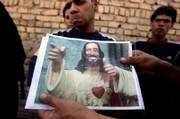"A man displays an image of the character known as ""Buddy Christ,"" which local residents claim was left by U.S. forces after a raid in Baghdad&squot;s Sadr City. ""Buddy Christ"" is a religious icon from the 1999 film ""Dogma."""
