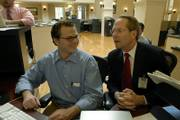 Christian Morgan, left, confers with Jim Barnett, Republican candidate for Kansas governor, as they respond to questions posed by ljworld.com readers. Morgan, campaign manager for Barnett, typed Barnett's dictated responses during a chat Monday at the News Center, 645 N.H. To read a transcript of the chat, go to ljworld.com.