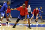 Kansas University freshman Sherron Collins practices defensive slides during a Boot Camp drill in Allen Fieldhouse. To his right is fellow frosh Darrell Arthur. The Jayhawks rose bright and early for Monday's 6 a.m. workout, part of a 10-day conditioning program designed to test the team's physical and mental limits.