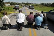 People kneel and pray on White Oak Road in Nickel Mines, Pa. A milk-truck driver carrying three guns and a childhood grudge stormed a one-room Amish schoolhouse Monday, sent the boys and adults outside, barricaded the doors with two-by-fours, and then opened fire on a dozen girls, killing three people before committing suicide. Another girl died later Monday. The schoolhouse is at upper left in the photo.
