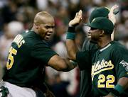 Oakland's Frank Thomas, left, and Milton Bradley celebrate the Athletics' 3-2 victory over the Minnesota Twins. Thomas hit two homers in the AL division series opener Tuesday in Minneapolis.
