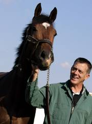 Dean Richardson, chief surgeon at the University of Pennsylvania's New Bolton Center for Large Animals, looks at Kentucky Derby winner Barbaro during an outing at the center.  Barbaro has been at the center for more than four months, and the leg that was shattered in the Preakness has all but healed.