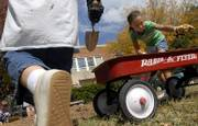 Pinckney School second-grader Sierra Smith shovels dirt into a Radio Flyer wagon as she and her classmates participate in a dig in the front lawn of the school. The students were digging Tuesday in an effort to find artifacts relating to the school's history.