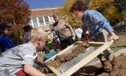 Pinckney second-graders Alex Bowen, left, and Henry Mackinnon sift through a heap of dirt in the front lawn of the school under the supervision of teacher Sharon Daniels. Several classes went digging Tuesday in the schoolyard in a hunt for artifacts from the school's original building, which was just south of the current school at 810 W. Sixth St.