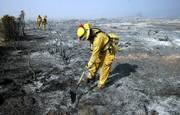 Chula Vista City firefighters check hot spots at the Day Fire near Ojai, Calif., in this Sept. 27 photo. A government official said Tuesday that wildfires in the continental United States burned a record number of acres this year, for a cost of more than $1.5 billion, also a record.