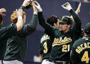Oakland's Mark kotsay (21) accepts congratulations on his two-run inside-the-park home run. The Athletics defeated the Minnesota Twins, 5-2, on Wednesday in Minneapolis.