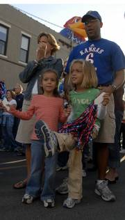 Lawrence residents front left, Bailey Sarna, 6, and Abby Monroe, 5, and Jerlyn and Michael Monore cheer along with the Rock Chalk dancers, the KU Cheerleaders and others while a block party was held to help promote KU's Homecoming game against Texas A & M at 11 a.m. tomorrow at Memorial Stadium.