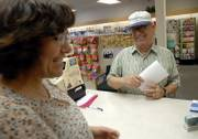 "Herman Morgan, Lawrence, picks up some information on his and his wife&squot;s prescription medication costs and visits with Penny Wingert, a technician at Orchards Drug, 1410 Kasold Drive. ""So far it&squot;s worked,"" Morgan said of his Medicare Part D plan."