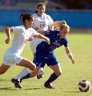 Kansas University's Lacey Novak (12) attempts to elude Texas defender Stephanie Logterman (10). The Longhorns topped the Jayhawks, 1-0, Friday at KU.